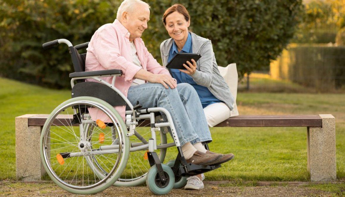 Caregiver and senior man on park bench, using digital tablet