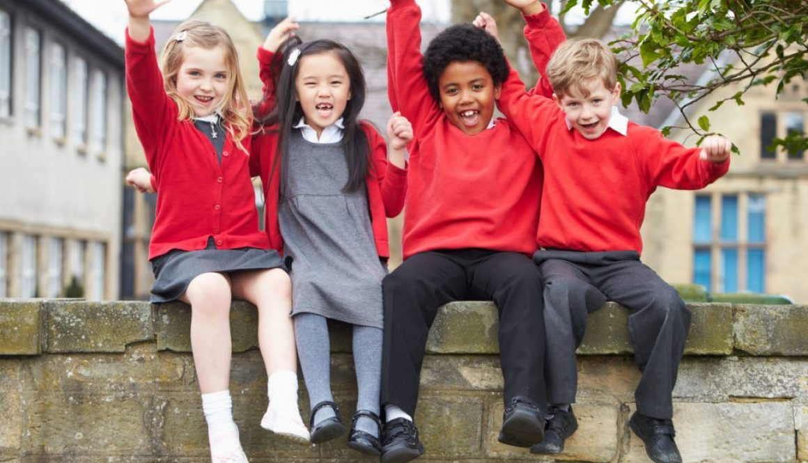 Portrait Of School Pupils Sitting On Wall Together