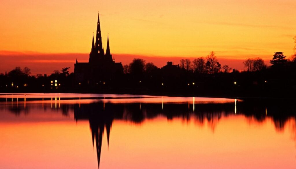 View of the spires of Lichfield Cathedral across Stowe Pool at sunset.